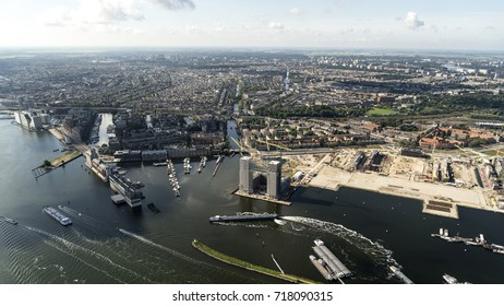Aerial view of Amsterdam, the Dutch capital, with the new landmark Pontsteiger in the Houthavens. A clear sky with cumulus and some cloud shadows on the ground.