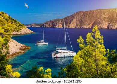 Aerial view of anchored sailing yacht in emerald sea. Aerial view of a boat. Outdoor water sports, yachting. Aerial view of anchoring yacht in open water. Ocean and sea travel and transportation