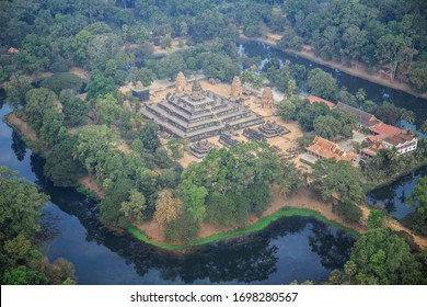 An aerial view of an ancient, massive stone Buddhist temple shaped like a pyramid and surrounded by a wide moat in the jungle near Angkor Wat in Siem Reap, Cambodia.