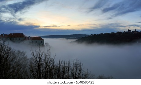 Aerial view of the ancient Znojmo Castle, built on the steep bank of the Thaya river, shot on a foggy winter day during sunset. Znojmo, South Moravia, Czech Republic, Europe.