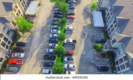 Aerial view of apartment garage with full of covered parking, cars and green trees of multi-floor residential building at sunset in US. Urban infrastructure and transportation concept. Panorama view.