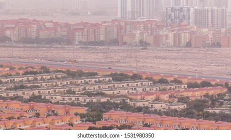 Aerial view of apartment houses, mosque and villas in Dubai city timelapse near jumeirah lake towers district, United Arab Emirates. Top fiew from skyscraper with traffic on highway
