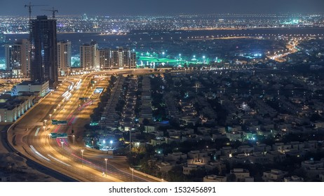 Aerial view of apartment houses and villas in Dubai city night timelapse near jumeirah lake towers district, United Arab Emirates. Top fiew from skyscraper with traffic on highway