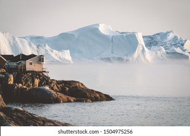 Aerial View of Arctic city of Ilulissat, Greenland during sunrise sunset with fog. Colorful houses in the center of the town with icebergs in the background in summer on a sunny day with orange pink