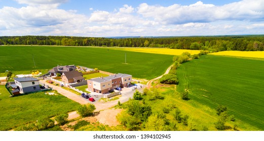Aerial view of area for pleasant living in suburban district. Houses with beautiful gardens and green fields in agricultural landscape.