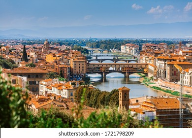 Aerial view of the Arno river and its bridges. Beautiful city landscape of Florence. The brown roofs of houses, cathedrals and bridges of Florence