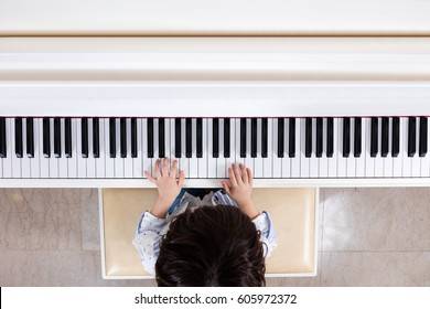 Aerial view of Asian Chinese little boy playing piano at home