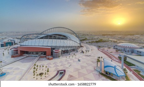 Aerial view of Aspire Zone from top at sunrise timelapse in Doha. Traffic on the road and car parking. Foggy weather