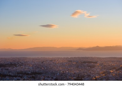 Aerial view of Athens (Greece), with Pireus port and Mediterranean Sea, with sunset sky and three clouds.