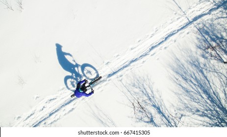 An aerial view of an attractive woman riding their fat bikes on a trail in the snow.