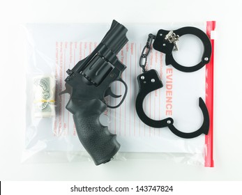 aerial view of a bag marked evidence containing a roll of money, a revolver and a pair of handcuffs with their keys, on a white background