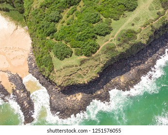 Aerial view of Bai Xep in a sunny day with emerald green ocean, black stone and whitecap waves surround the hill cover by green plant - a wonderful destination in Phu Yen province, Vietnam