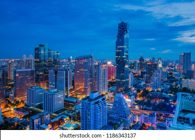 Aerial view of Bangkok Cityscape with modern office buildings in twilight time, condominium in city downtown with sunset sky, Bangkok, Thailand.
