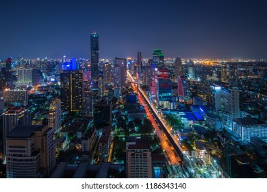 Aerial view of Bangkok Cityscape with modern office buildings in night, condominium in city downtown with sunset sky, Bangkok, Thailand.
