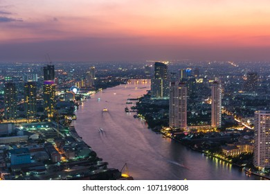 Aerial view of Bangkok cityscape at sunset with Chao Phraya river and colourful sky. Modern urban background