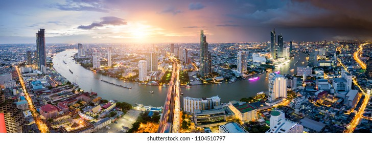 Aerial view of Bangkok skyline and skyscraper with light trails on Sathorn Road center of business in Bangkok downtown. Panorama of Taksin Bridge over Chao Phraya River Bangkok Thailand at sunset.