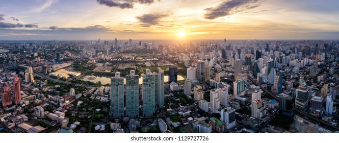 Aerial view of Bangkok skyline and skyscraper on Sukhumvit center of business in capital. Panorama of modern city and BTS skytrain with Benjakiti park on Asoke junction at Bangkok Thailand on sunset
