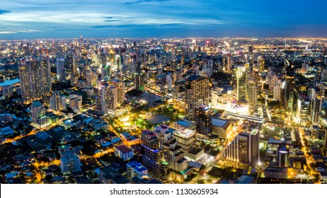 Aerial view of Bangkok skyline and skyscraper on Sukhumvit center of business in capital. Panorama of modern city and BTS skytrain with Benjasiri park on Asoke junction in Bangkok Thailand at night