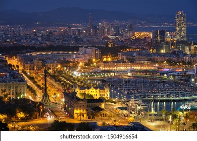 Aerial view of Barcelona city skyline with city traffic and port with yachts illuminated in the night. Barcelona, Spain