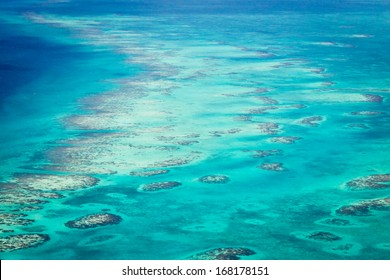 aerial view of the barrier reef of the coast of San Pedro, Belize. with large waves breaking away from the coast