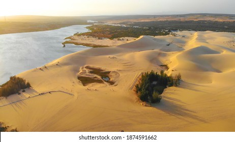 Aerial view of Bau Trang lake (a beautiful landscape, raw of automobiles with blue sky in desert, beautiful landscape of white sand dunes), the popular tourist attraction place in Mui Ne, Vietnam.