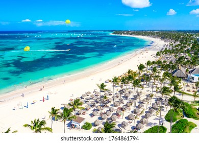 Aerial view of Bavaro beach Punta Cana tropical resort in Dominican Republic. Beautiful atlantic tropical beach with palms, umbrellas and parasailing balloons