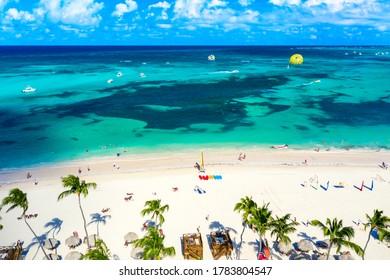 Aerial view of Bavaro beach Punta Cana tropical resort in Dominican Republic. Beautiful atlantic tropical beach with palms, umbrellas and parasailing balloon