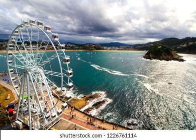 Aerial view at the bay of San Sebastian, Basque country, Spain. With the observation wheel on the foreground and picturesque scenery of the coastline on the background.
