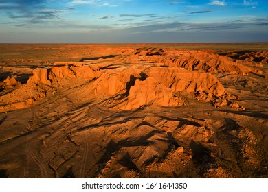 Aerial view of the Bayanzag flaming cliffs at sunset in Mongolia, found in the Gobi Desert.