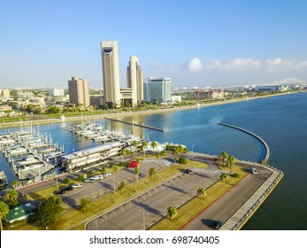 Aerial view Bayfront area of Corpus Christi with skylines and marina piers filled row of boat, sailboat and yacht at sunrise. City harbor bridge far right in distance. A Texas city on Gulf of Mexico.