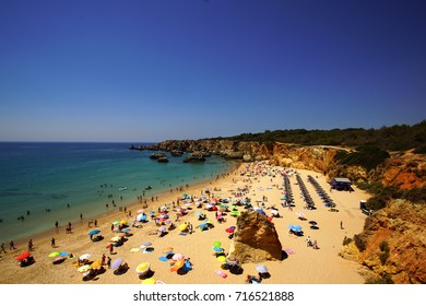 Aerial view of a beach in Algarve with tourists and colourful umbrellas