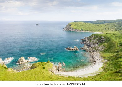 Aerial view of beach in beautiful bay on green coast with rocks and turquoise sea. Sunny summer seaside landscape in Asia. Gamov Peninsula in Primorsky Krai, Far East, Russia