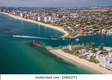 aerial view of beach and boaters at hillsboro inlet on atlantic ocean in florida with lighthouse