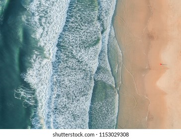 Aerial view of a beach with breaking waves