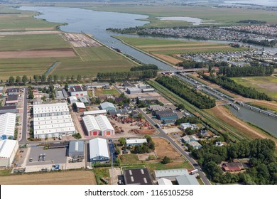 Aerial view beach Dutch village Lemmer with industrial park, lake, sluice, canal, and marina harbor