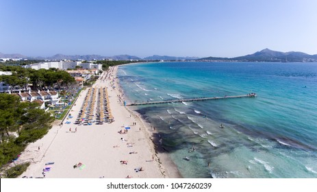 Aerial view to beach, full of umbrellas and people in summer