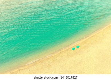 Aerial view of beach lounge with umbrellas on tropical golden paradise beach with turquoise waters - vacation and holiday concept with privacy and quiet heaven travel destination island for couples