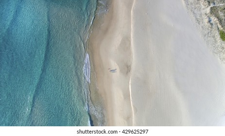 Aerial view of beach ocean waves and people walking on sand on Gold Coast beach