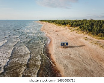 Aerial view of beach in Palanga city, with sand dunes, Baltic sea waves and pine tree forest surrounding.