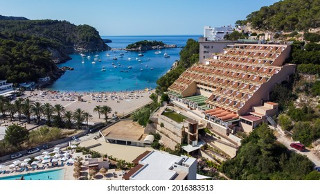 Aerial view of the beach of Port Sant Miquel on the north shore of Ibiza island in Spain - Isolated bay sided with large hillside hotels in the Balearic Islands