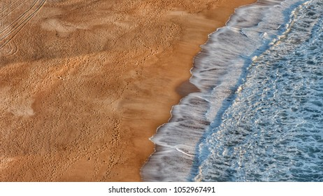 Aerial view of beach sand and water on day waves crashing