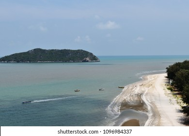 Aerial view of beach and sea at Laem Sala Beach , Ship traveling in the sea  , Small island with blue sky and fluffy cloud in background , Khao Sam Roi Yot National Park , Thailand