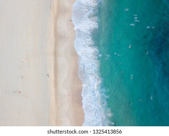 Aerial view of beach shore with clear water in a summer day.