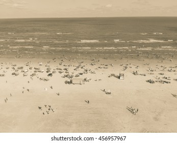 Aerial view beach shoreline on sunny summer day with people bathing, sunbathing, playing volley and relax in Galveston, Texas. Colorful umbrellas, lounge chairs. Holiday maker, summer vacation concept
