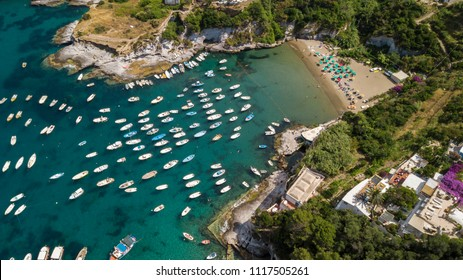 Aerial view of the beach and the small harbor of Cala Feola on the island of Ponza, in Italy. There are many boats and motorboats of tourists anchored in the bay and sheltered in the mountains.
