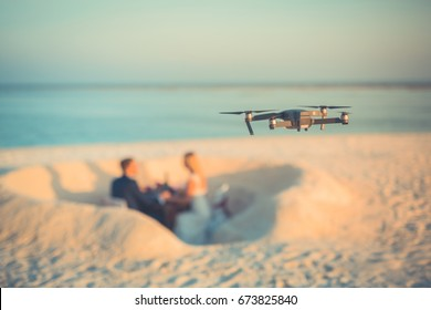Aerial view of beach wedding. Drone photography of a lovely wedding couple. Heart shape in the sand, sunset mood