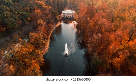 Aerial view of the beautiful autumn orange landscape park with a pond and a fountain in the center, Uman, Ukraine