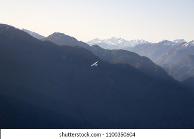 Aerial view of the beautiful Canadian Mountain Landscape with an airplane flying. Taken North of Vancouver, British Columbia, Canada.