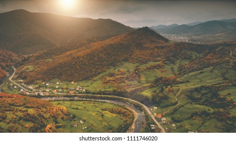 Aerial View: Beautiful canyon village located along the river. Dramatic autumn mountain landscape with green meadows, orange pine tree forests, sunset cloudy sky. Carpathians, Ukraine, Europe.