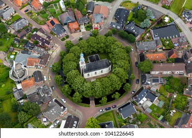 Aerial view of beautiful dutch village Spijk in the province of Groningen, Holland. The town is built on a terp or mound and has a church in the center of the hill. It has a circle pattern.